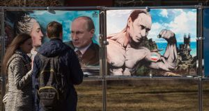 A couple stands by pictures depicting Russian president Vladimir Putin at an open-air political cartoons exhibition dedicated to the one-year anniversary of Crimea voting to leave Ukraine and join the Russian state in central Moscow. Photograph: Dmitry Serebryako/AFP/Getty Images