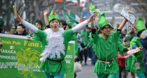 People wearing green march during a St Patrick's Day parade in Tokyo, Japan. Photograph: Kazuhiro Nogikazuhiro/AFP/Getty Images
