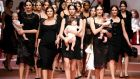 'Pregnant models stalked down the catwalk, and instead of carrying dinky little handbags, some of the models toted beautiful babies.'  Photograph: REUTERS/Alessandro Bianchi