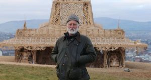 Artist David Best stands beside his intricately handcrafted 72ft  wooden temple in Derry ahead of its burning. Photograph: Niall Carson/PA Wire