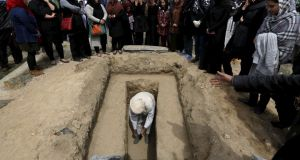 A man prepares for the burial of Farkhunda. Photograph: Mohammad Ismail/Reuters