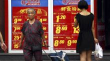 Shoppers walk past and look at a board displaying food prices at a shopping mall in central Beijing. Photogrpah: David Gray/Reuters