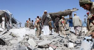 Soldiers and Houthi fighters inspect the damage caused by air strikes on the airport of Yemen's northwestern city of Saada, a Houthi stronghold near the Saudi border, on Monday. Fighter jets attacked the Yemeni capital of Sanaa, residents said. Photograph: Reuters