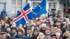 Protesters march under an Icelandic and EU flag on Austurvoellur square, across from the Icelandic parliament, in Reykjavik earlier this month, after the government announced plans to withdraw the country's application for EU membership. Photograph: Anton Brink/EPA