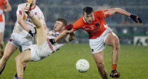 Tyrone's Cathal McShane grapples with Armagh's Ethan Rafferty. Photograph: Inpho