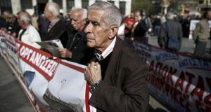 A pensioner holds a banner during an anti-austerity demonstration in Athens yesterday. Greece is expected to reach agreement with its euro zone partners and the IMF on a package of reforms next week. Photograph: Alkis Konstantinidis/Reuters