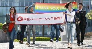 "Hiroko Masuhara and Koyuki Higashi hold a banner reading ""Congrats on the same-sex partnership statute"" after a Tokyo area recognised same-sex partnerships. Photograph: Kyodo/Reuters"