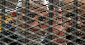 Egypt's Muslim Brotherhood leader Mohamed Badie flashing the four-finger sign from behind dock bars during a trial session in Cairo, Egypt. Photograph: EPA/STR