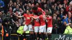 Chris Smalling is mobbed by his Manchester United team mates after he scored United's fourth in their 4-2 win over Manchester City. Photograph: Afp