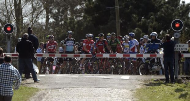 The peleton is stopped at a level crossing as a train approaches in the Paris_Roubaix one day classic. Photograph: Afp