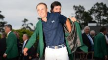 Last years champion Bubba Watson helps Jordan Spieth put on the Green Jacket of the 2015 Masters Champion at the 79th Masters Golf Tournament at Augusta National Golf Club. Photo: Jim Watson/Getty Images