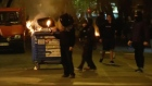 Black-clad self-styled anarchists hurl petrol bombs and rocks at police on the streets of Athens. Video: Reuters