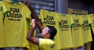 "A vendor hangs shirts reading ""Out, Dilma"" during a protest against Brazil's president Dilma Rousseff over a corruption scandal at Petrobras. Photograph: Reuters"