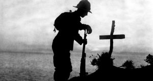 A British soldier paying his respects in 1915 at the grave of a colleague near Cape Helles,  where the Gallipoli landings took place. Photograph: PA