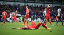 Liverpool's Dejan Lovren lays on the ground dejected after the final whistle during the Barclays Premier League match at The Hawthorns. Photo: Nick Potts/PA