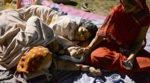 Two women rest and sleep in a football field in Siliguri on Sunday  hit the region on April 25th.  Photograph: AFP/Getty Images