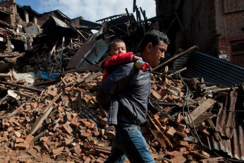 A man carries a child as he walks past destroyed buildings in Bhaktapur, on the outskirts of Kathmandu. Photograph: Niranjan Shrestha/AP