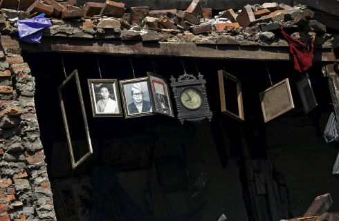 Photographs and a clock hanging inside a damaged house in Bhaktapur. Photograph: Adnan Abidi/Reuters
