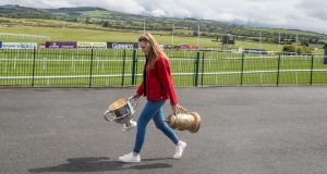 Sarah Kelly carries  trophies into Punchestown for the annual racing festival. Photograph: Michael Chester