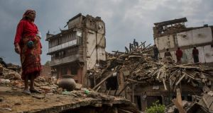 A woman stands amidst the damage to a neighbourhood in Bhaktapur in Nepal where  residents are working to recover personal belongings from their severely damaged homes. Photograph: Daniel Berehulak/The New York Times.