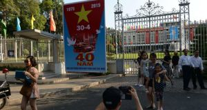A family poses next to a poster marking the 40th anniversary of the fall of Saigon (now Ho Chi Minh City) placed at the front gates of the former presidential palace of the Southern Vietnamese regime in Ho Chi Minh Cit. Photograph:  Hoang Oang Dinh Nam/AFP/Getty Images