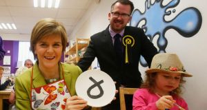 SNP party leader Nicola Sturgeon with three-year-old Kitty MacDonald and SNP candidate for the Glasgow South constituency Stewart McDonald during a visit to Glazed, a ceramic painting studio in Glasgow. Photograph: Danny Lawson/PA Wire