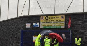 Bus drivers on strike in the rain at the Phibsborough depot in Dublin on May 2nd.