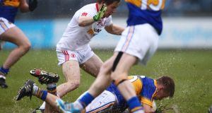 Tyrone's Kieran McGeary keeps an eye on Paul Maher as the Tipperary man slides along the wet turf of Parnell Park. Photograph: Cathal Noonan/Inpho