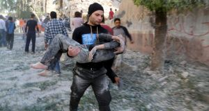 A man holds an injured boy after what activists said was a barrel bomb dropped by forces loyal to Syrian president Bashar al-Assad hit a school and residential building in the Seif al-Dawla neighborhood of Aleppo. Photograph: Hosam Katan/Reuters