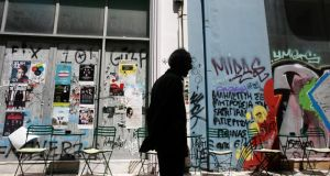Graffiti covers the shopping windows of closed shops, as a pedestrian walks past, in Athens, Greece. Euro-area officials were sceptical that a technical agreement would be reached by Wednesday.  Photograph: Kostas Tsironis/Bloomberg
