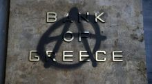 An anarchy symbol spray-painted over the logo of Bank of Greece in Athens. Most top credit rating agencies say they would not cut Greece's rating to default if it misses a payment to the IMF or ECB. Photograph: Reuters