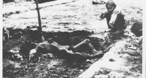 A murdered Armenian man lies in a ditch as a  child watches the corpse. Photograph: Armin Wegner / Armenian National Institute, courtesy of Sybil Stevens