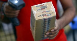 A worker of Indian e-commerce company Snapdeal.com scans barcode on a box after it was packed at the company's warehouse in New Delhi – after losing top talent to Silicon Valley, an e-commerce boom is sparking a thriving start-up culture in India. Photograph: REUTERS/Anindito Mukherjee
