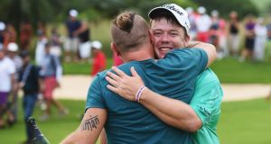 South African golfer George Coetzee celeberates with his compatriot, rock star Ard Matthews,  after Coetzee's victory at the AfrAsia Bank Mauritius  Open at Heritage Golf Club yesterday. Photograph:  Stuart Franklin/Getty Images