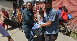 Patients are carried out of a Kathmandu hospital building following Tuesday's 7.3 earthquake in Nepal. The quake struck at 12:35pm local time 83 km east of the city near Mount Everest. It was followed by several aftershocks. Tuesday's quake comes more than two weeks after at least 8,000 people were killed in an earthquake in the Himalayan country.  Photograph: Prakash Mathema/AFP/Getty Images