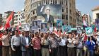 Syrians holding portraits of President Bashar al-Assad as they gather in the central city of Homs around the city's newly renovated clock tower during a ceremony revealing the restored monument. Photograph Getty Images