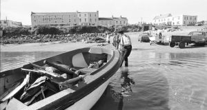 Victims of the bombing:  a garda pulls ashore a rowing boat containing wreckage of Shadow V, Lord Mountbatten's boat, at Mullaghmore. Photograph: Pat Langan