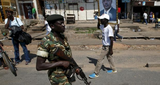 Streets of Burundi's capital, Bujumbura: a supporter of president Pierre Nkurunziza carries his picture as a solider patrols the streets. Protesters have been told they will be fired upon. Photograph: Goran Tomasevic/Reuters