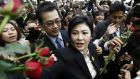 Former Thai prime minister Yingluck Shinawatra (C) receives flowers from supporters as she leaves after a hearing on criminal charges stemming from her government's rice price subsidy at the Supreme Court's Criminal Division for Holders of Political Positions in Bangkok on Tuesday. Photograph: EPA