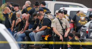 "A McLennan County deputy stands guard near a group of bikers in the parking lot of a Twin Peaks restaurant Sunday, May 17th, 2015, in Waco, Texas. Waco Police Sgt W Patrick Swanton told KWTX-TV there were ""multiple victims"" after gunfire erupted between rival biker gangs at the restaurant. Photograph: Rod Aydelotte/Waco Tribune-Herald via AP"