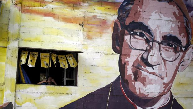 A man closes a window in the wall next to a mural of the late Salvadoran Archbishop Oscar Arnulfo Romero in Panchimalco, on the outskirts of San Salvador. Photograph: Jorge Dan Lopez/Reuters
