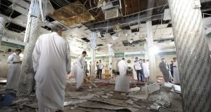 Saudi men examine debris following a blast inside a Shia mosque in the Saudi Gulf coastal town of Qatif on Friday. Photograph: AFP Photo