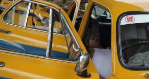 An Indian taxi driver rests in his parked car in Kolkata on Monday. Taxi unions in the city have urged drivers to stay off the roads between 11am and 4pm because of the heat after a driver died in his cab. Photograph: AFP Photo/ Dibyangshu Sarkar
