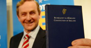 Taoiseach Enda Kenny holding a copy of Bunreacht na hÉireann, which will now contain gender-neutral language in relation to the institution of marriage. Photograph: Bryan O'Brien