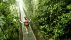 A young woman hikes along a hanging bridge near Arenal Volcano National Park in Costa Rica.