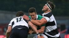 Barbarians' Wynand Oliver and Gerhard Vosloo tackle Ireland's Colm O'Shea during the friendly match at Thomond Park.