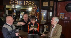 "William ""Spud"" Murphy, barman Christy Hynes, Sam O'Connor and Richard Whyte in Mulligan's bar. Photograph: Cathy Dunne/Jill Kenny"
