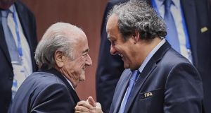 Veteran Fifa president Sepp Blatter shakes hands with Uefa president Michel Platini after being re-elected on Friday. Photograph: Getty Images