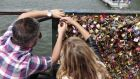 A couple locks a padlock on the Pont des Arts in Paris. Photograph: Charly Triballeau/AFP/Getty Images