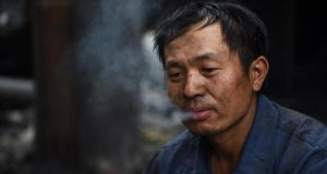 A worker smoking during a break at a demolition site in Beijing. Data shows that about 1.5 million people die from smoking-related diseases every year in China, where there are 300 million smokers. Photograph: Greg Baker/AFP/Getty Images